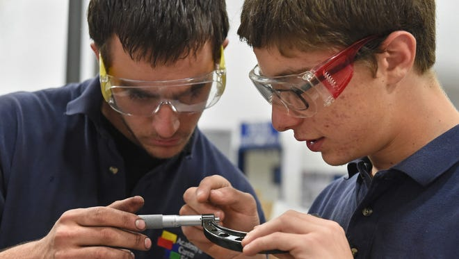 ACE charter high school students Jared Cuddy, left, and Joshua Nissim work in a diesel class in 2016. The school's upcoming classes will receive free shuttle rides to school thanks to a partnership with the school, My Ride to Work and Tesla.