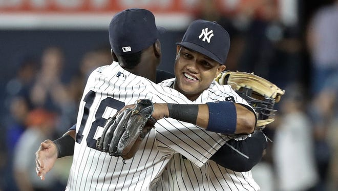 New York Yankees' Starlin Castro, right, and Didi Gregorius, left, celebrate after a baseball game against the Baltimore Orioles Tuesday, July 19, 2016, in New York. The Yankees won 7-1.
