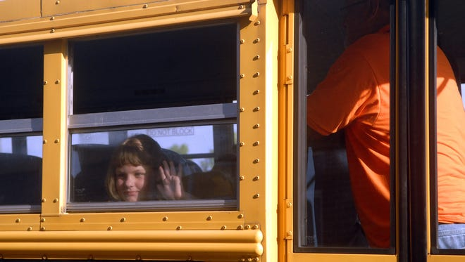 A student waves to a classmate Wednesday as she waits to get off the bus on the first day of school at Shepherdsville Elementary School.