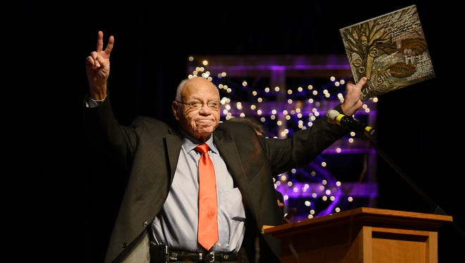 "Herman Boone, former T.C. Williams High School head football coach and inspiration for the movie ""Remember the Titans,""  holds up a piece of art given as a gift by the Sacred Heart of Jesus High School art class at the conclusion of his speech during school's 2017 benefit banquet Tuesday evening."