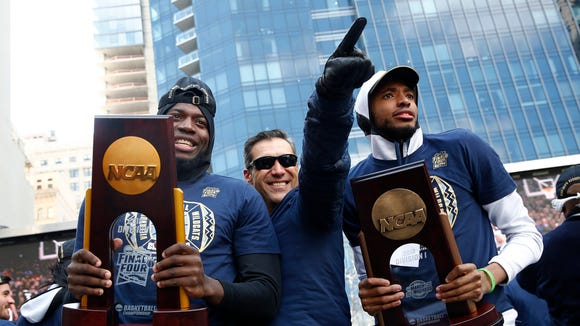 Villanova forward Eric Paschall, from left, head coach Jay Wright and guard Mikal Bridges acknowledge fans during a rally following a parade celebrating the team's NCAA college basketball championship, Thursday, April 5, 2018, in Philadelphia. Villanova defeated Michigan on Monday for the NCAA men's basketball title. (AP Photo/Patrick Semansky)