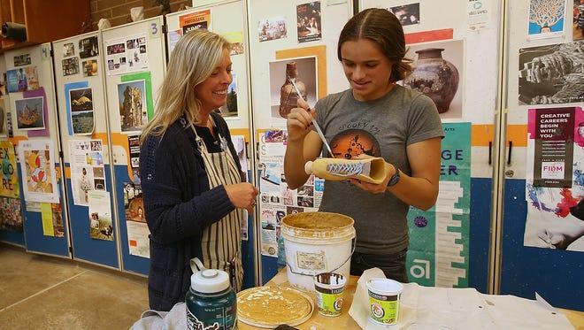 Bainbridge High School art teacher Elizabeth Ande talks with student Natalie Taylor as she works on a project during class.