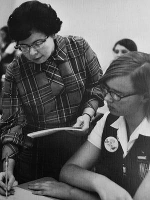 Eleanor Barrett helps a student find her error.