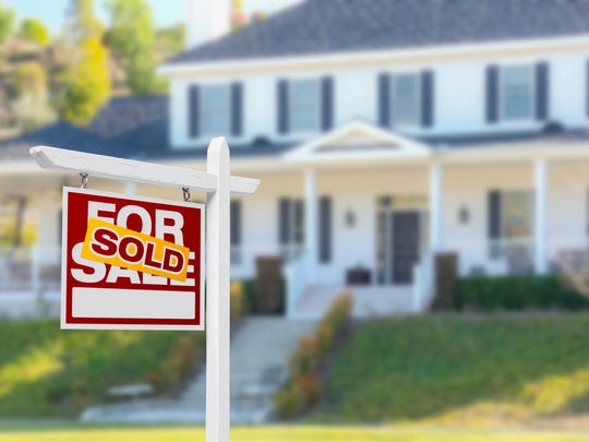 "A ""for sale"" sign with ""sold"" sticker in front of a home."