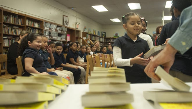 Third-grader Yarisel Urena, receives a dictionary from Camden City Rotary at the Veterans Memorial Family School in Camden. Enrollment is underway for city students.