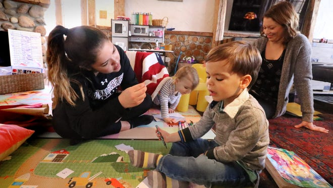 Kristin Gendreau (left), a UW-Milwaukee student and therapy technician, works with James Crimmins, 3, as part of his home therapy for his autism to prepare him to attend school with his peers. A whiteboard lists all of the behavioral skills that James therapy focuses on. Sally Kubasa, a behavioral treatment therapist, and James' sister Lily interact in the background.
