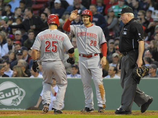 Reds left fielder Chris Heisey (28) waits at home plate to congratulate center fielder Skip Schumaker (25) after hitting a two run home run during the third inning against the Boston Red Sox at Fenway Park.