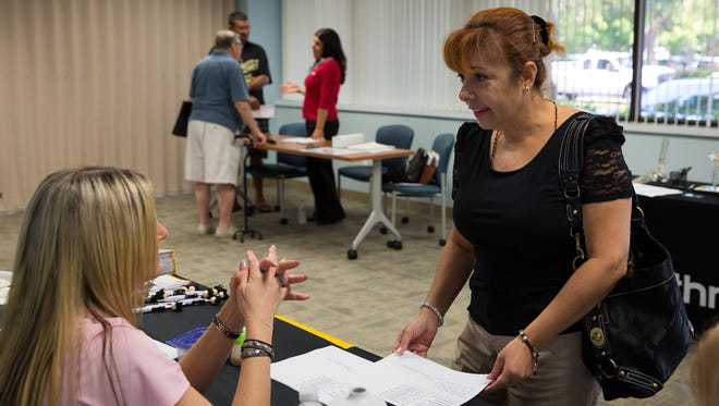Martha De La Barrera, of Naples, inquires about employment with representatives from the Parker Hannifin manufacturing company at a job fair at CareerSource Southwest Florida in this May 18, 2016, file photo.