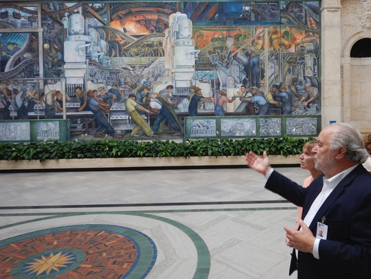 A docent explains the history of the Diego Rivera murals