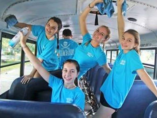 St. Edward's School freshmen Michaela Miller, left, Chloe Secunda, Morgan Chapman and Miranda Morey clean the inside of the Gifford Youth Achievement Center bus on Nov. 1.