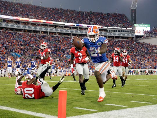 Florida Gators running back Kelvin Taylor (21) runs the ball for a touchdown against the Georgia Bulldogs during the second half at EverBank Stadium. Florida Gators defeated the Georgia Bulldogs 27-3.