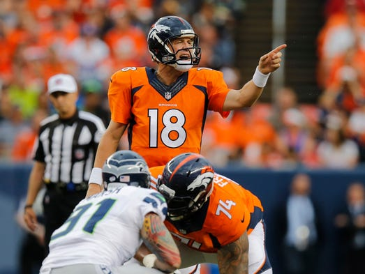 Denver Broncos quarterback Peyton Manning (18) calls a play against the Seattle Seahawks during the first half of an NFL preseason football game, Thursday, Aug. 7, 2014, in Denver.