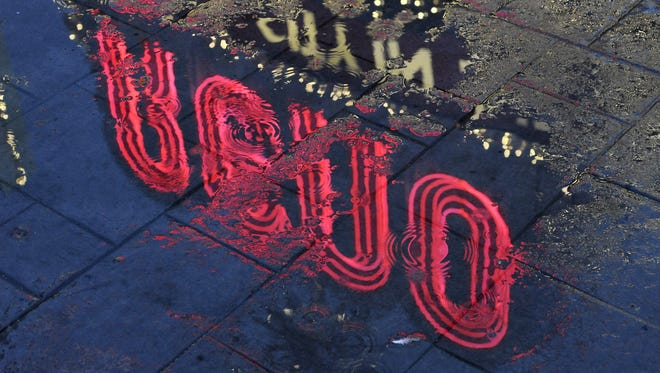 The Reno Arch is reflected in a puddle of water on a rain-covered sidewalk in downtown Reno on Monday, Jan. 18, 2010.