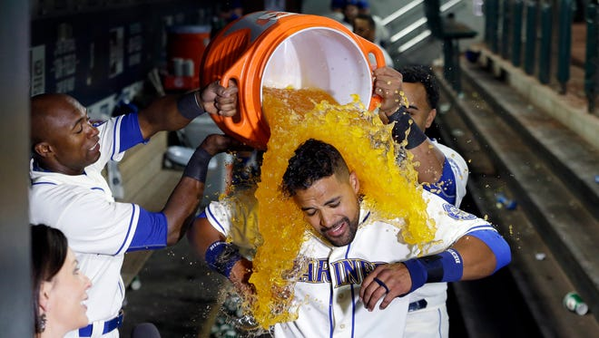 Seattle Mariners' Franklin Gutierrez, center, is doused with a bucket of a sports drink by teammates Austin Jackson, left, and Nelson Cruz after Gutierrez's home run that beat the Toronto Blue Jays in the 10th inning of a baseball game Sunday, July 26, 2015, in Seattle. The Mariners won 6-5.
