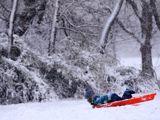 Three-year-old Henry Moates tries to wiggle around on his sled, without success, to get it to go farther down the hill at Barfield Crescent Park on Friday, Jan. 22, 2016, in Murfreesboro.