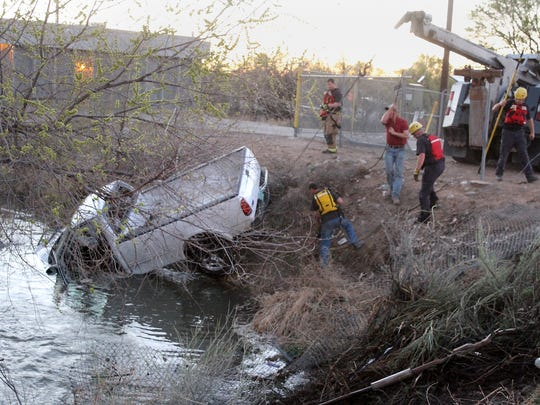Workers extract a Ford F-150 pickup from the Willett Ditch Saturday after a three-car crash just off East Broadway Avenue in Farmington.