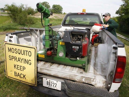 Kyle Newman loads a sprayer after spraying pellets