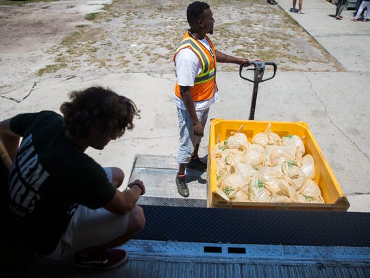 Farm Share volunteers Cole Wessel, left, and Dwayne Young, right, help unload food during the Farm Share distribution and RCMA event at Guadalupe Social Services on Thursday, April 26, 2018.