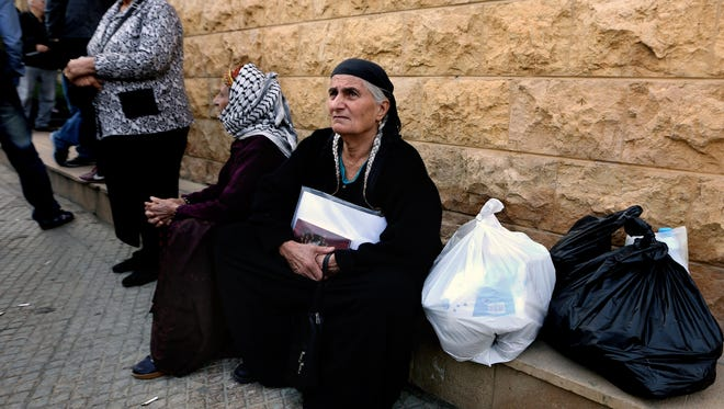 Chaldeans who fled their homes in Iraq  wait for humanitarian aid distribution at the Chaldean Archbishopric in Baabda, east of Beirut, Lebanon, on Tuesday, March 17, 2015.  Syrian and Iraqi Christians are pleading for more international assistance after arriving in Lebanon to escape Islamic State militants.
