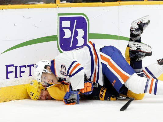 Nashville Predators left wing Cody McLeod (55) and Edmonton Oilers defenseman Matt Benning (83) slide into the boards as they chase the puck during the second period of an NHL hockey game Thursday, Feb. 2, 2017, in Nashville, Tenn. (AP Photo/Mark Humphrey)
