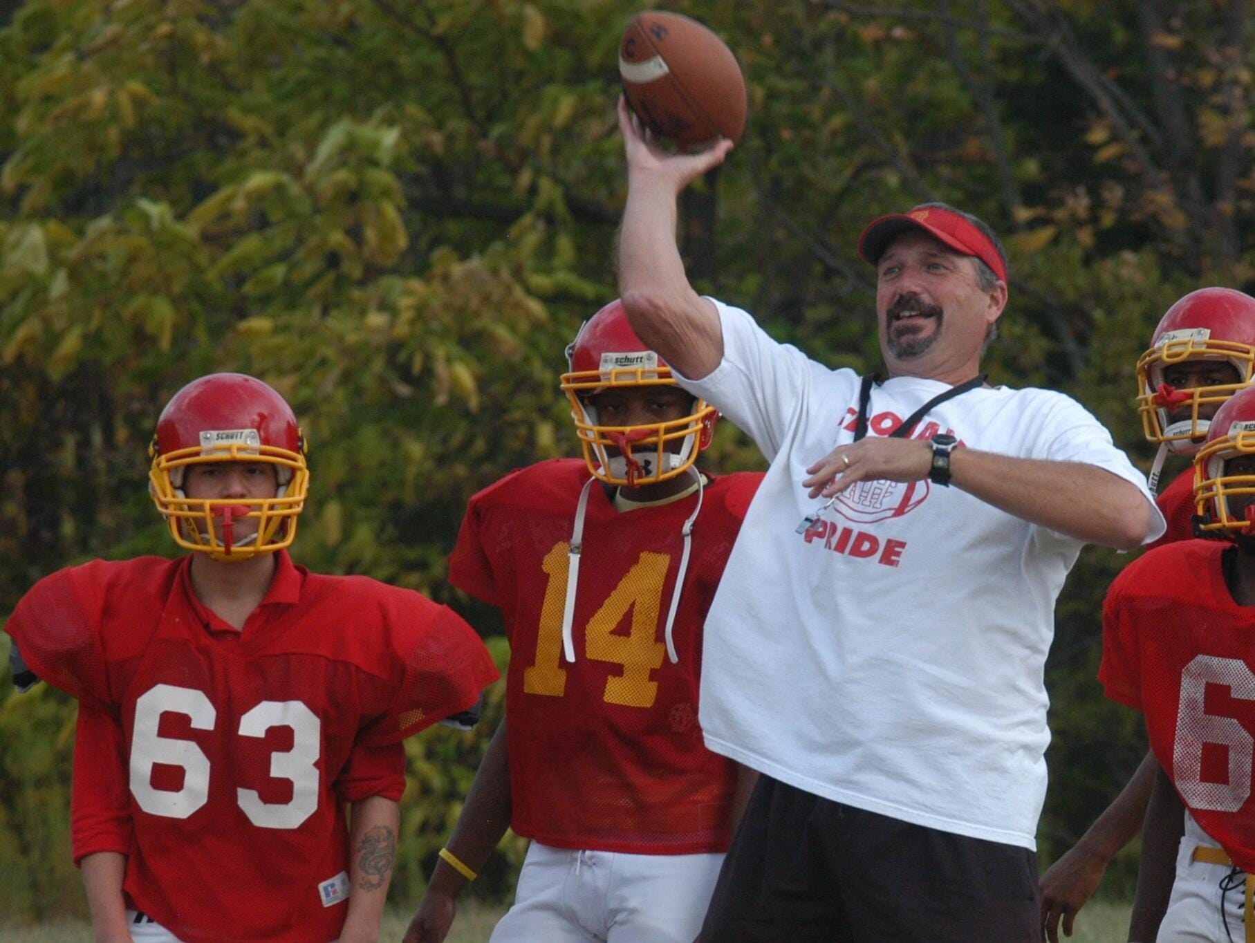 Shown in 2010, North College Hill head football coach Bruce Baarendse performs a passing drill with his players at practice.
