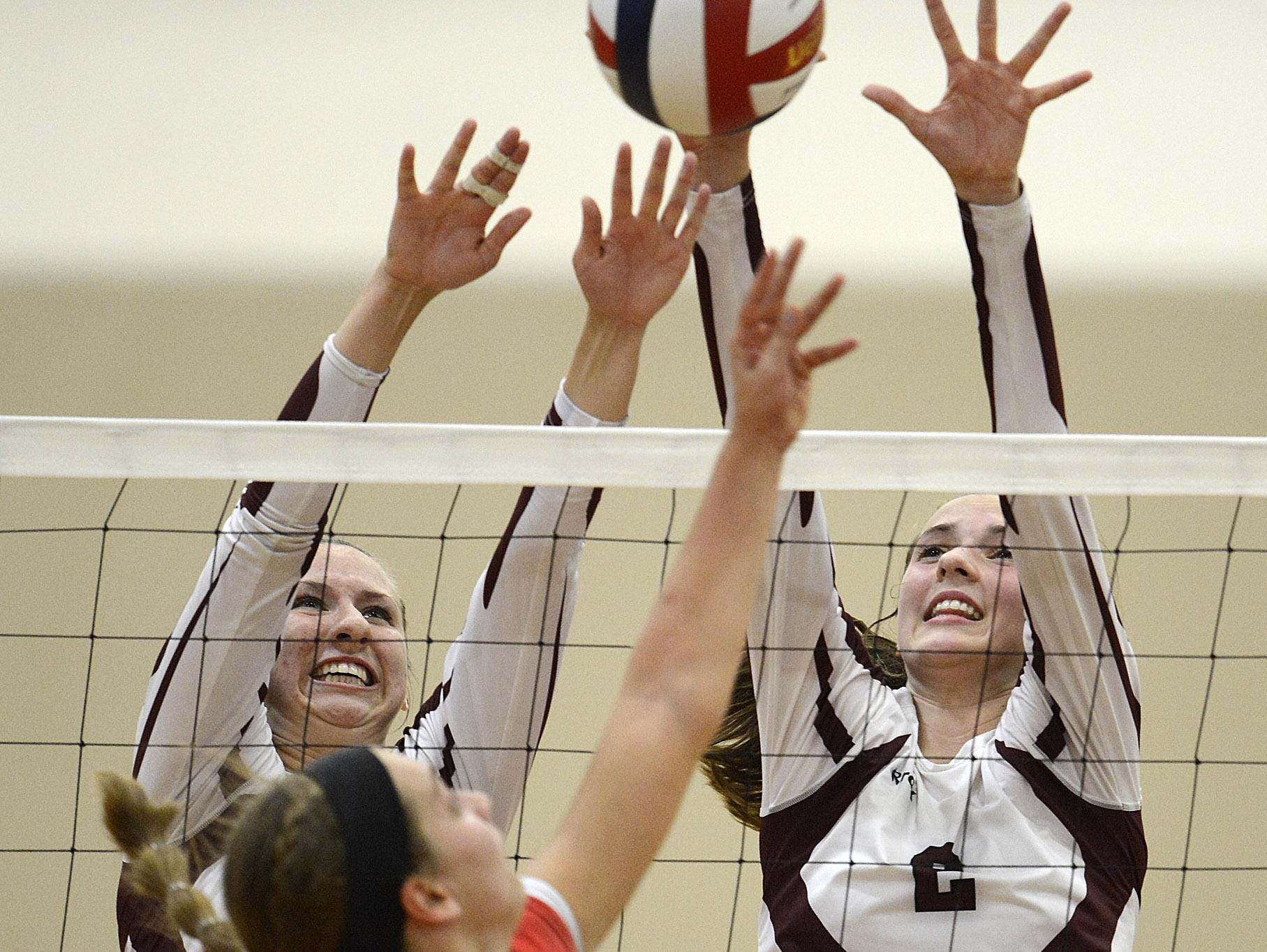 De Pere's Lindsey Mirkes (2) and Ashley Smits (4) team up to block a shot attempt by Manitowoc's Cassidy Mrotek (9) during Thursday night' volleyball match at De Pere.