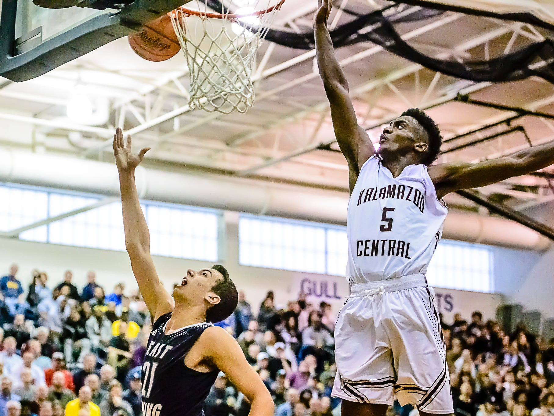 Westin Myles ,left, of East Lansing clangs the ball off the rim as he attempts a layup while being defended by Ontarion Burnett ,5, of Kalamazoo Central late in the 3rd quarter of their Class A Regional Final game with Kalamazoo Central leading 47-34 Wednesday March 15, 2017 at Gull Lake High School in Richland. KEVIN W. FOWLER PHOTO