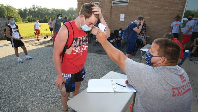 Magnus Lloyd, 14, at left, gets his temperature taken by assistant football coach Bill Frick, seated, before the start of a football workout Thursday at General McLane High School in Washington Township. All sports teams in Pennsylvania are following safety protocols, including the wearing of face masks and social distancing when not competing, and daily temperature checks to slow the spread of COVID-19, the new coronavirus.