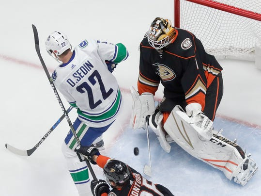 Anaheim Ducks goalie Reto Berra, right, blocks a shot by Vancouver Canucks left wing Daniel Sedin during the third period of an NHL hockey game in Anaheim, Calif., Thursday, Nov. 9, 2017. The Ducks won 4-1. (AP Photo/Chris Carlson)
