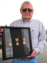 """William """"Gus"""" Gustafson holds his metals that he received over 50 years after his service during the Cold War. Tuesday, Dec. 5, 2017."""
