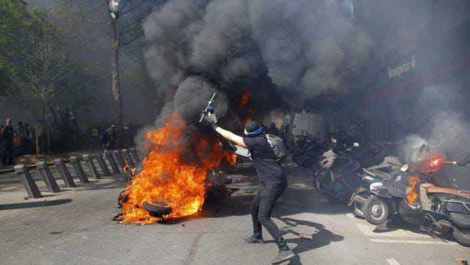 A protestor throws a scooter onto a pile of burning motorbikes during a yellow vest demonstration in Paris, Saturday, April 20, 2019.
