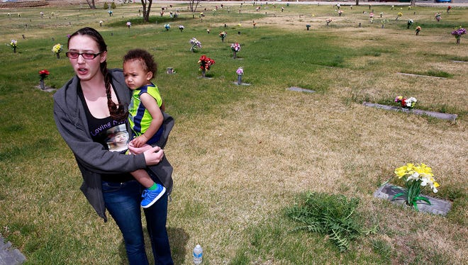 Lizzy Sanchez and her son, L.C. Hemingway, 1, on Friday stand next to the grave of Lizzy's daughter, Princess RoseaLee Jane Mitchell, who was buried at Memory Gardens in June of 2014. A group of plot owners have been protesting conditions at the cemetery at 6917 E. Main St.