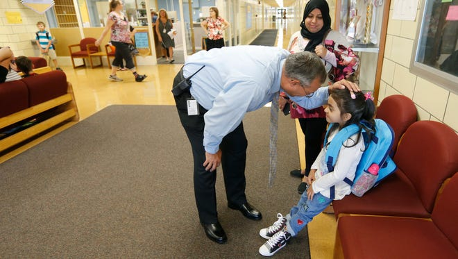 Principal Brian Hill talks to kindergartner Suroor Musa, 5, as her mother Huda Alfhod watches during the first day of school at Crane Elementary School in Henrietta. They are originally from Iraq and the school takes pride in its diversity.
