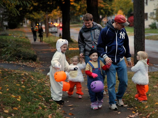 Paul Conrow holds Amanda's hand as they walk along Garson Avenue trick-or-treating on Halloween. Amanda was dressed as Agnes from the movie Despicable Me. Her little sister, Emily, her cousins and their dad walk along with them.