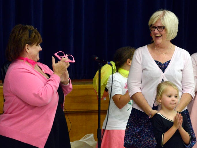 St. Mary School principal, Courtney Tielke, left, introduces school secretary, Becky Basche during a 1950's theme sock hop in honor of her 60th birthday Friday at the school, Aug 29, 2014.