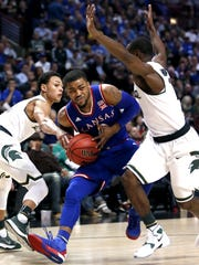 Kansas guard Frank Mason III, center, looks to the basket as Michigan State's Bryn Forbes, left, and Tum Tum Narin defend Tuesday night in Chicago.
