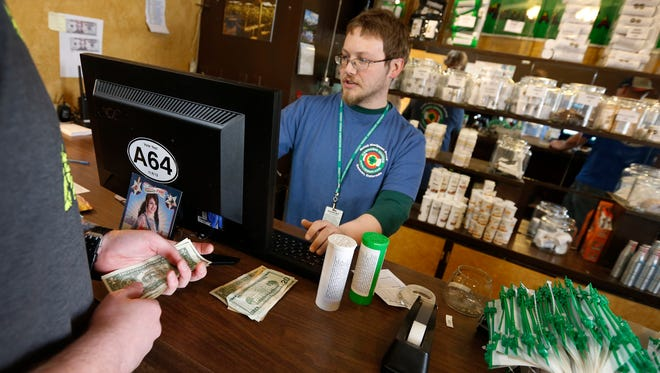 A customer pays cash for retail marijuana at 3D Cannabis Center, in Denver on Thursday, May 8, 2014. Frustrated by the cash-heavy aspect of its new marijuana industry, Colorado is trying a long-shot bid to create a financial system devoted to the pot business.