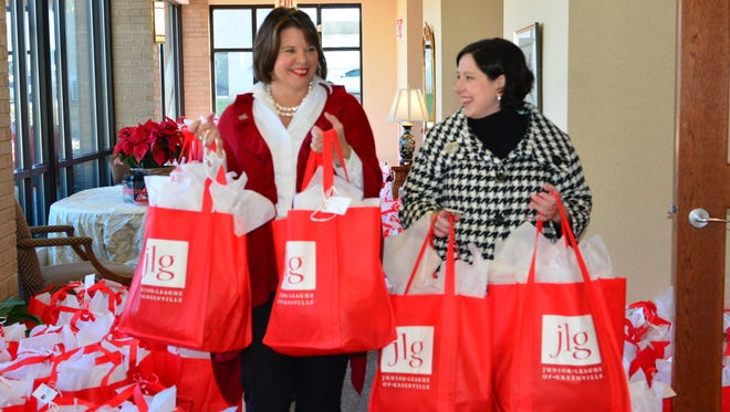 Junior League of Greenville members Kimberly Cooley, left, and Rebecca Feldman carry some of the Christmas gift bags the organization has prepared for local cancer patients.