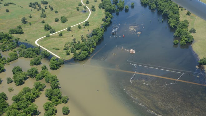 A white boom in the foreground appears intended to contain a spill last year during flooding on the Trinity River, but the measure appears inadequate. The Texas Department of Public Safety has removed such photos from a public website, citing privacy concerns.
