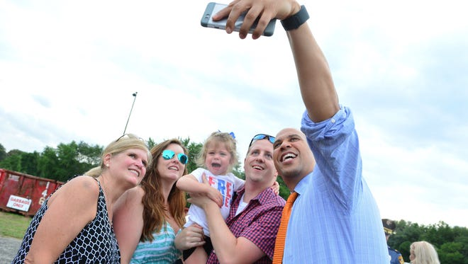 (NEWS)         08/10/16             Ocean, NJ U.S. Sen. Cory Booker (far right/D-N.J.) takes a selfie with (from left) Lee Wheeler, Jennifer Kelly, Amelia Kelly (2) and Michael Kelly, all of Tinton Falls, during a visit to the Italian- American Festival in Ocean on Wed.  Frank Galipo/Correspondent ASB 0811 Booker Monmouth I