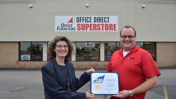 Standing in front of Office Direct in Stevens Point, CAP Services' Laura West presents business owner Cole Corrigan with a certificate recognizing the business as the winner of CAP's first Business Expansion Contest.