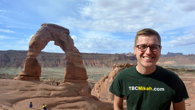 Mikah Meyer, who is on a quest to visit all 417 national park sites across the U.S. and its territories, poses at Arches National Park in Utah.