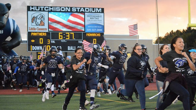 The Piedra Vista football team takes the field with miniature U.S. flags in hand for Friday's homecoming game at Hutchison Stadium.