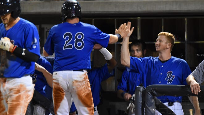The Blue Wahoos Mitch Nay (28) is congratulated by teammates after scoring a run in the second game Wednesday night of doubleheader sweep over Biloxi Shuckers.