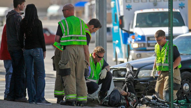 Emergency crews work to stabilize a bicyclist who police say was struck by a car on Monday at the intersection of North Auburn Avenue and West Main Street in Farmigton.