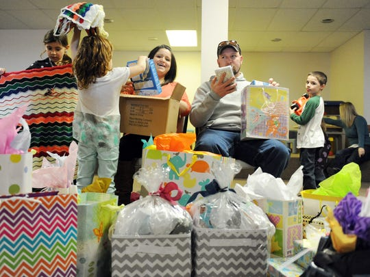 """ERIN McCRACKEN / COURIER & PRESSSara and Zach McCarter open up gifts at their baby shower for their twins, Blaine and Mila on at St.Vincent Catholic Church in Vincennes, Ind., on Feb. 7, 2015. """" I think we may need a bigger house,"""" Zach said as he looked at the pile of presents and duplicate gifts for each baby. The couple have gone through a lot with finding a surrogate and getting pregnant and are anxious for their children to arrive in early April."""