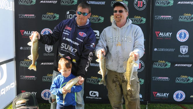 Pro angler RJ Harwood with his son Hayden show off fish with co-angler Steve Beasley after the weigh in on the first day of the Cabela's National Walleye Tour Championship held in Oshkosh.