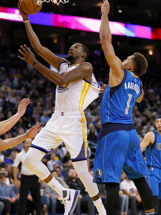 Golden State Warriors forward Kevin Durant (35) drives to the basket against Dallas Mavericks guard Justin Anderson (1) during the second half of an NBA basketball game in Oakland, Calif., Friday, Dec. 30, 2016. (AP Photo/Tony Avelar)