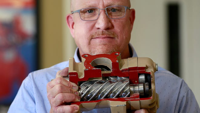 Roger Armstrong, general manager of Twin Stars, on June 10 holds a rotary screw compressor similar to the type used in the Vapor Recovery Units the company, located at 100 Iowa Ave. in Bloomfield, sells and maintains.
