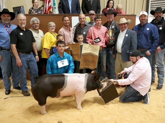 Jonah Menchaca, Post FFA, sold the reserve grand champion market barrow for $13,000. Pictured are Michael Strauss, H-E-B; George Sweet, 1st Community Federal Credit Union; Raymond Meza, Twin Mountain Fence; Patsy McIntire, Bug Express; John Myer, Myer Ranch; Phil Gandy, Gandy Ink; Menchaca; Cameron Menchaca; Josiah Menchaca; Bandy Osborn; Joe Self, Automatic Fire Protection; Mike Martin, Goode Construction; Todd Price, Jim Bass Cars and Trucks; Wes Pullig, Fire House Auto; and Kevin Allbright, Auto Wrangler.